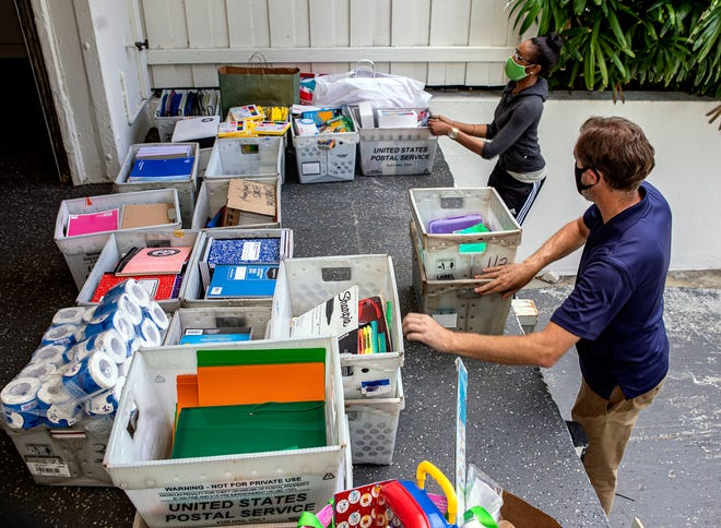 Eric Roby and Melissa Marks of the Boys & Girls Clubs of Palm Beach County pick up school supplies from the Town of Palm Beach United Way in August 2020. The clubs serve 395 children from low-income families.
