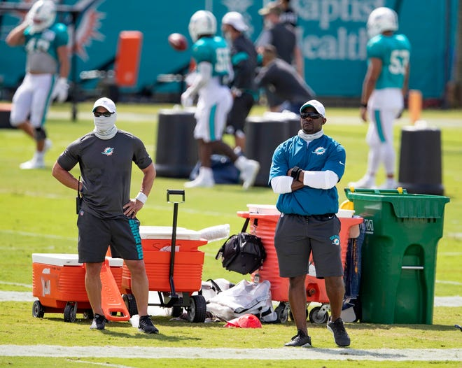 Dolphins coach Brian Flores, right, watches practice during last summer's training camp, which was closed to fans due to COVID-19