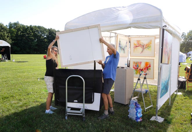 Mixed-media artist Jennifer Gardner of Florida gets a hand from her husband, Geoff, as the two begin to hang artwork in their booth Friday evening at the Wickford Art Festival.