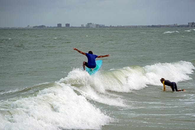 Luis Ernesto catches a small wave while surfing along Pass-a-Grille Beach, Wednesday, July 7, 2021 in St. Pete Beach, Fla., the morning after Tropical Storm Elsa moved over the Tampa Bay Area. The Rhode Island Department of Environmental Management is warning that Elsa will generate high surf and rip currents along the Rhode Island shore into Saturday.