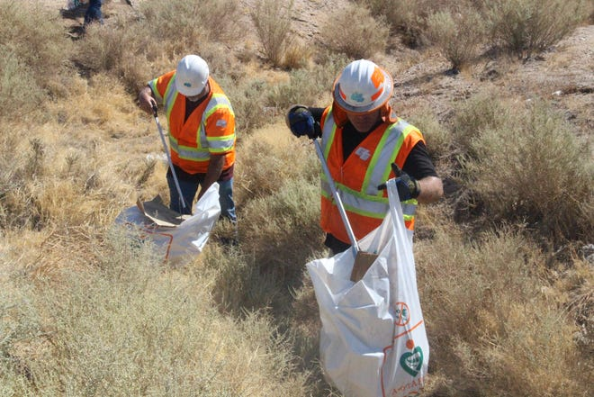 """Workers clean litter on July 7, 2021 along Inyokern Road in Ridgecrest to kick off the state's """"Clean California"""" initiative."""