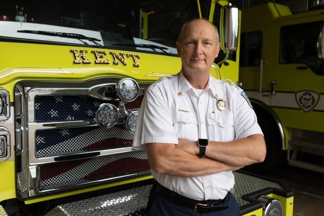 Retiring Kent Fire Chief John Tosko stands in front of one of the department's trucks. Tosko will be leaving in early August, 33 years after joining as a firefighter.