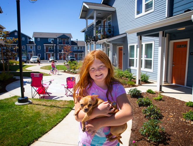 Nine-year-old Kaylee Spence and neighbor dog Harley play in the courtyard of the recently completed Hayden Bridge housing project in Springfield.