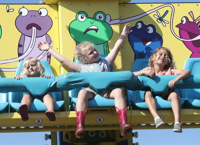 Area kids got a kick out of the Frog Hopper ride Thursday afternoon at the Olde Canal Days festival. Two-year-old Willow Sutton (left), Cami Linville, 6, and Grayson Sutton, 5, took their turn on the ride not long after the sun popped out at Heritage Park.