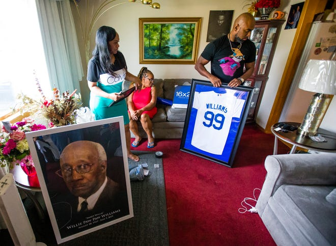 Ronin Johnson Jr. prepares a jersey display for his late grandfather, Willie Williams, along side Kathy Kirkendoll, left, and Sheila Stokes Friday, at the Williams family home in South Bend.