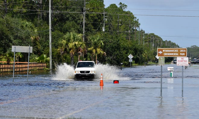 A truck drives through floodwater on Tropicaire Boulevard, in North Port, on  July 10. Water from the Myakkahatcheee Creek flows south across the road. Streets near the creek were flooded as rain from Hurricane Elsa continued to drain.