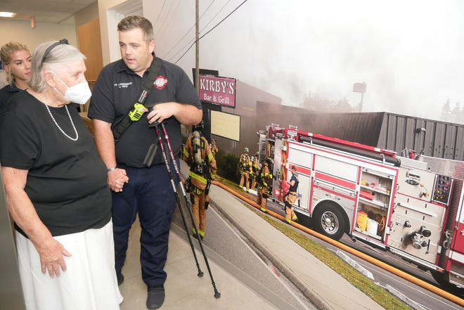 Ginger Spencer, president of the board of directors for the Siesta Key Fire and Rescue Advisory Council, looks at a mural-sized photo depicting firefighters in action on the second floor of Fire Station 13 on Siesta Key, Friday morning. Spencer, who has been on the 47-year-old advisory board since 1982, was escorted through the station by Sarasota County Firefighter/Paramedic Jeremy Rice and Sarasota County Firefighter/EMT Samantha Worsham.
