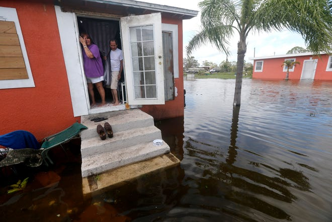 A couple looks at the flooding outside their home in the aftermath of Hurricane Irma in Immokalee.