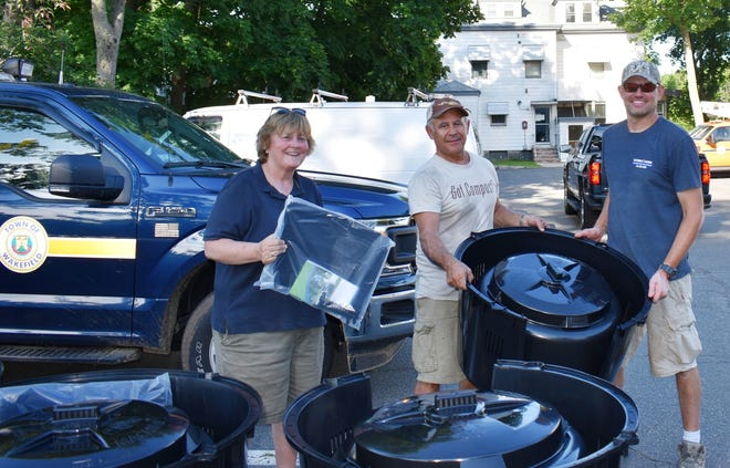 Wakefield resident Frank Giangregorio, right, picked up his compost recycling bin from Wakefield Department of Public Works' Business Manager Ann Waitt, left, and Jeffery Brown, center, of BrandBuilders during the DPW's scheduled pickup. The bins were offered to Wakefield residents at a discounted price through the DPW's partnership with Earth Machine.