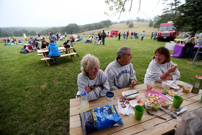 Ann Fickenwirth of Hull, Helmut Fickenwirth of Hull, and Connie Cummings of Hingham share a laugh and good food during the sunset picnic at Weir River Farm on Thursday, July 8, 2021.