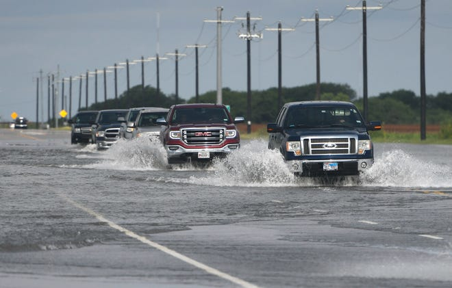 Trucks attempt to drive through flooding on Staples, Friday, July 9, 2021, in London. A flash flood watch continues for the area, according to the National Weather Service.