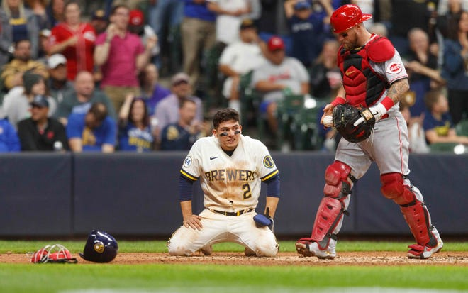 Jul 8, 2021; Milwaukee, Wisconsin, USA;  Mllwaukee Brewers second baseman Luis Urías (2) reacts after being tagged out by Cincinnati Reds catcher Tucker Barnhart (16) while trying to score a run during the seventh inning at American Family Field.