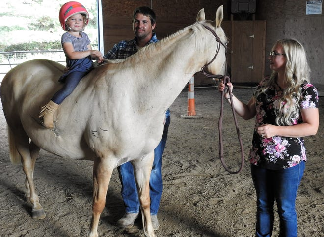 Luke and Emily Schmalzied monitor their 3-year-old daughter, Lael, as he rides Faith, a horse saved from slaughter. The couple operates Moving Mountains Ranch, which offers therapeutic riding to youth and would like to expand services to those in drug rehabilitation, veterans, first responders and more.