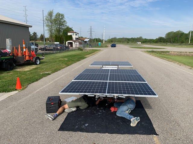 William Jones and Kyle Samluk underneath their solar power car, Pink Skies.