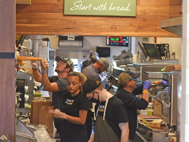 The staff of Panera Bread is hard at work trying to keep up with the Friday lunch rush.