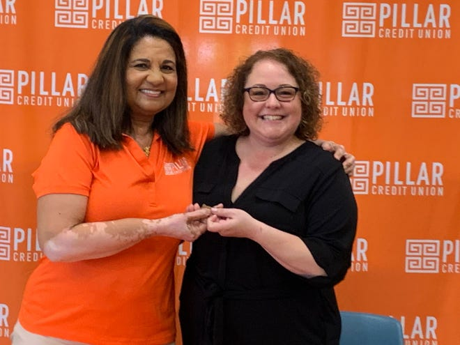 Pillar Credit Union President and CEO Vidya Iyengar gives a key to Marion Matters Executive Director Heidi Jones during a signing ceremony May 18, 2021. After closing its branch at 810 Kenton Ave. earlier this year, the credit union decided to turn over the building to the nonprofit organizaton.