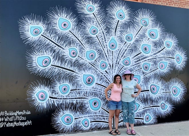 Amy Hagenow, left, poses with artist Kelsey Montague in front of the finished peacock mural on the side of the UW-Milwaukee Panther Arena. Hagenow was the first person to get a photo in front of the mural and has been a fan of Montague's work since 2017.