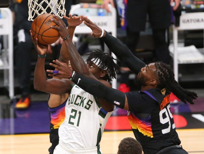 Milwaukee Bucks guard Jrue Holiday (21) grabs a rebound from Phoenix Suns forward Jae Crowder (99) during Game 2 of the NBA Finals at Phoenix Suns Arena July 8, 2021.