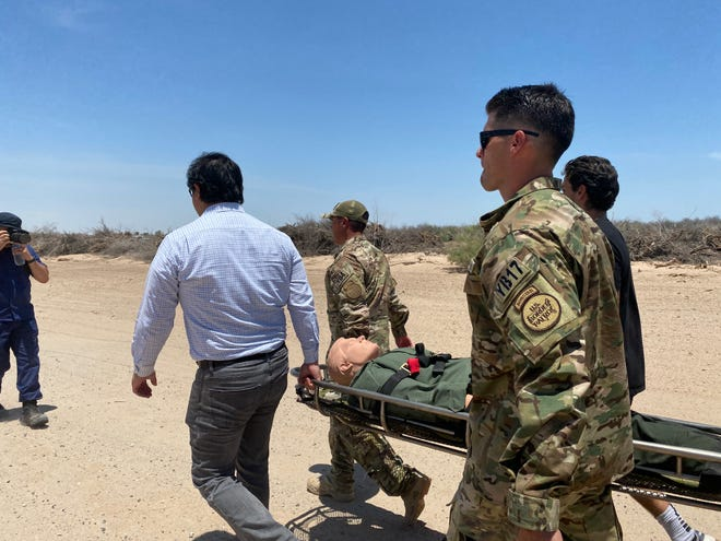 A dummy weighing 220 pounds is carried for several hundred yards to reenact what Border Patrol agents do when encountering a migrant who is ill. The simulation was part of an event on July 8, 2021, at the Arizona-Mexico border near Yuma emphasizing the danger of border crossing without documentation in extreme heat.