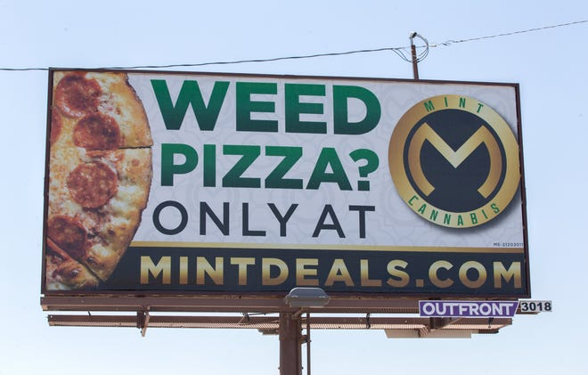 A Mint Cannabis billboard that promotes Weed Pizza is seen near Roosevelt Street in Phoenix on July 9, 2021.