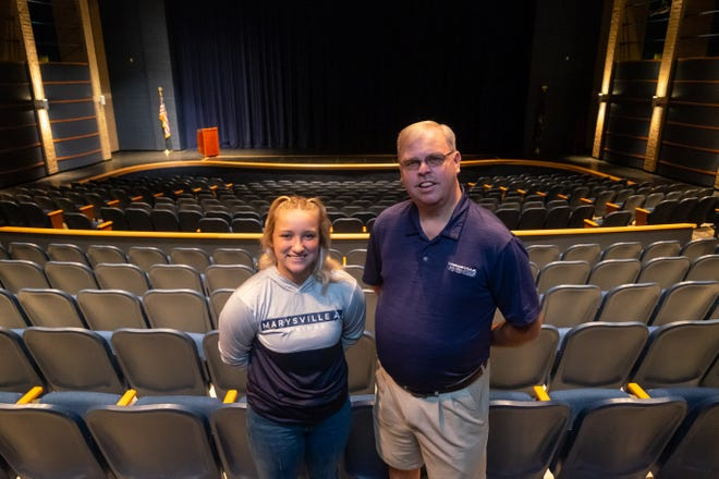 Kirk Smith, a teacher at Marysville High School, right, poses for a portrait with 2021 graduate Nicole Will Friday, July 9, 2021, in Marysville High School's auditorium. The two worked on a documentary about Marysville's volleyball team, which will be shown next week at the school.