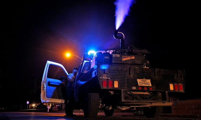Treg Marcilliotte, lower left, runs a fogging machine on Old Post Rd. during a mosquito control effort by the city of San Angelo on Thursday, July 8, 2021.