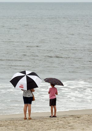 Visitors watch the waves on Rehoboth Beach as Tropical Storm Elsa approaches the Delaware Coast.