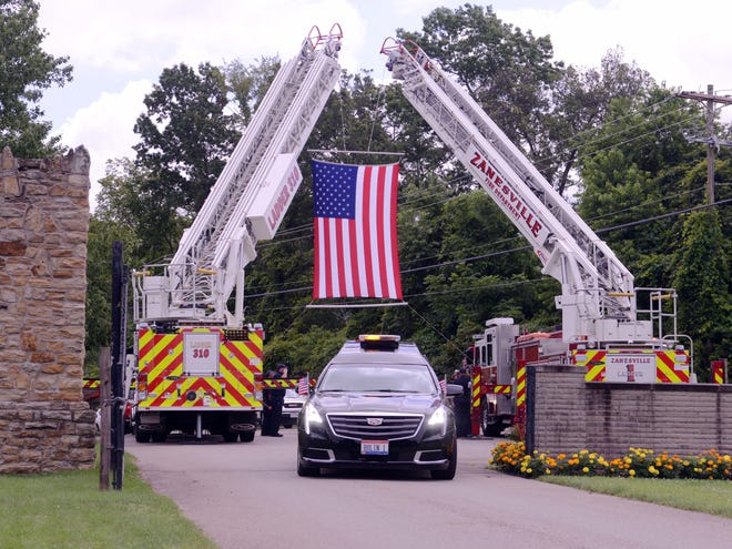 Martha Lentz, wife of retired Zanesville Assistant Fire Chief Robert Lentz, drives the hearse carrying her husband during his funeral services on Friday at Zanesville Memorial Park.