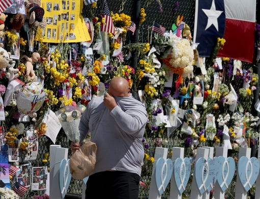 A person becomes emotional as he visits the memorial that includes pictures of some of the victims of the collapsed 12-story Champlain Towers South condo building on July 08, 2021 in Surfside, Florida. The death toll currently stands at 60 and 80 people are still missing as rescue workers have shifted the operation to recovery efforts.