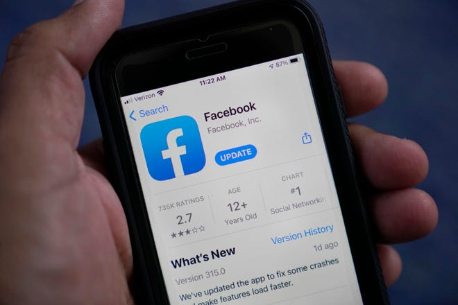 The Facebook app is shown on a smart phone, Friday, April 23, 2021, in Surfside, Fla. Since the start of the year, Twitter and Facebook have removed tens of thousands of accounts, groups and pages dedicated to the QAnon conspiracy theory. But QAnon is far from winding down.
