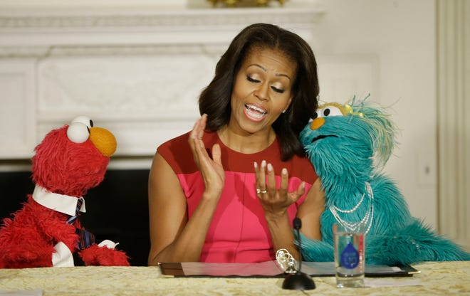 """First lady Michelle Obama with """"Sesame Street"""" characters Elmo and Rosita, help promote fresh fruit and vegetable consumption to kids in an event in the State Dining Room of the White House , Oct. 30, 2013. S"""