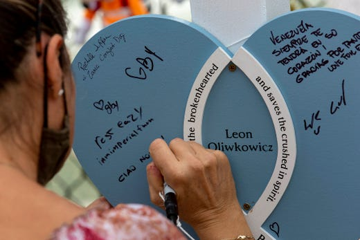 """A woman inscribes a note reading """"Caio Nonno!"""" (""""Hello Grandfather"""") on a memorial for Loen Oliwkowskicz at the Surfside Wall of Hope and Memorial for victims of Champlain Towers South condo collapse in Surfside, Florida Friday, July 9, 2021.  ORG XMIT: 2570966 (Via OlyDrop)"""
