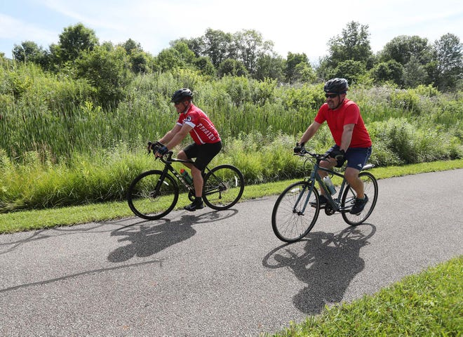 Roger Nudelman, left, of Twinsburg, and Mitch Stachan of Mayfield ride their bikes along the Summit Metro Parks Bike & Hike Trail Saturday, July 10, 2021 in Sagamore Hills, Ohio.