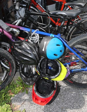 Several helmets are attached to a row of bicycles at a trailhead Saturday, July 10, 2021 in Peninsula, Ohio.