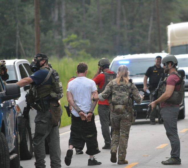 Police escort Christopher O'Donald to a patrol car after a short standoff.
