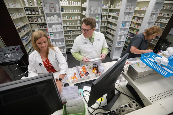 Nate Hux, center, talks with Kristen Pfeiffer at the Pickerington Pharmacy. Hux is among pharmacists across the nation who complain about clawbacks from pharmacy benefit managers.