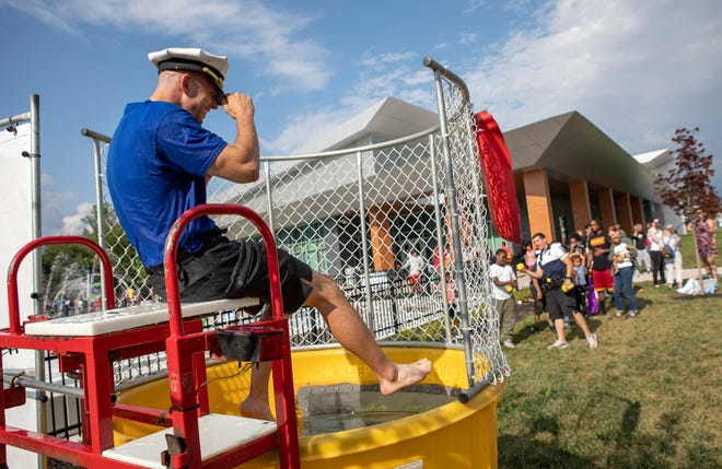 Officer Shawn Lutz sits in a dunk tank during a summer block party hosted by the Columbus Division of Police and the Starfish Assignment at the Linden Community Center in early July. Police and residents in Columbus and throughout the nation will come together again on Tuesday for National Night Out events geared to building good police-community relationships.