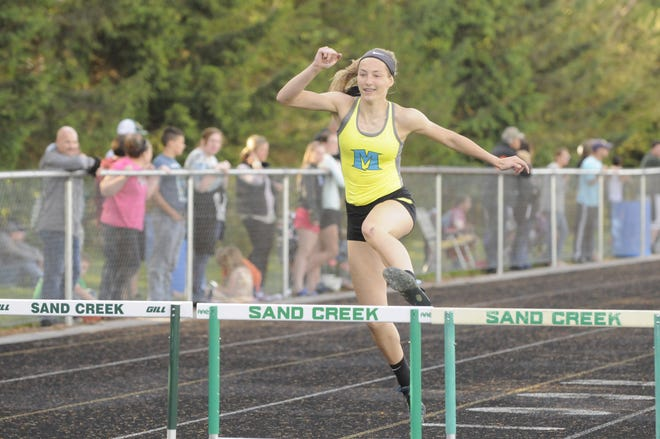 Madison's Carly Anschuetz leaps over a hurdle during a meet at Sand Creek during the 2019 season.