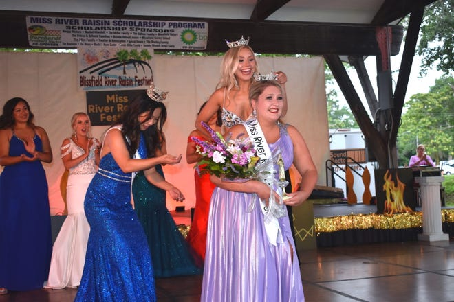 Laurel Hammis, 20, the daughter of Kelley and Joseph Hammis of Saginaw who will graduate from Adrian College in December, was crowned Miss River Raisin Festival 2021 out of a field of nine other Lenawee County young women vying for the program title Friday night during Blissfield's River Raisin Festival. Placing the crown on Hammis' head is 2019 and 2020 Miss River Raisin Festival Sydney Papenhagen of Blissfield. Miss Michigan 2021, Vivian Zhong, left, assists in the crowning ceremony.