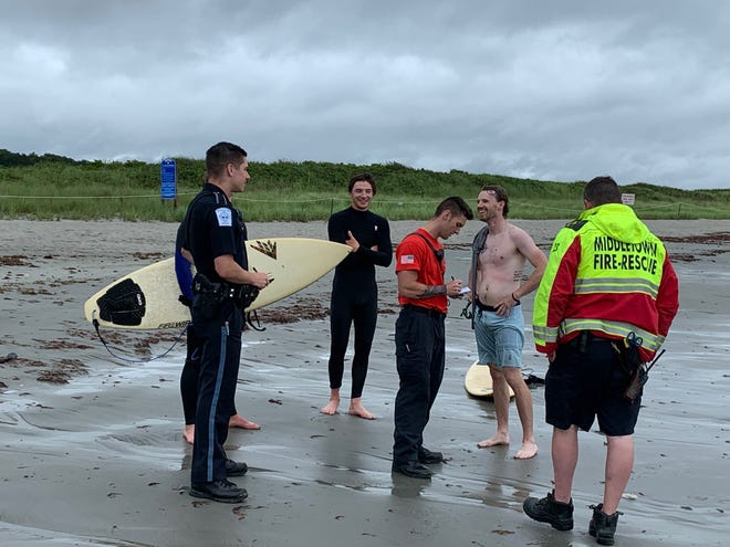 Rescue personal from Middletown talk with surfers after one Second Beach surfer was rescued Friday.