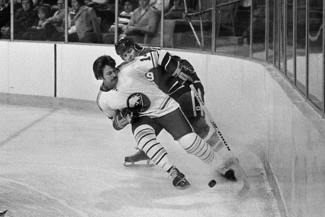 Rene Robert (front)  of the Buffalo Sabres beats Don Lever of the Vancouver Canucks to the puck during a 1977 NHL game. Robert played minor league hockey for the Tulsa Oilers.