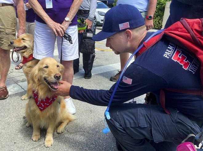 Palm Beach County firefighter Rain Flavin pets a comfort dog from the Lutheran Church Charities as he finishes his shift working in the rubbles of the Champlain Towers South collapse Thursday in Surfside.