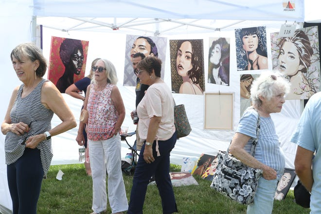 Visitors check out the work of artist Jillian Krenshaw on Saturday in day one of the 59th annual Wickford Art Festival, held in Wilson Park this year. The festival continues tomorrow, from 10 a.m. to 5 p.m.
