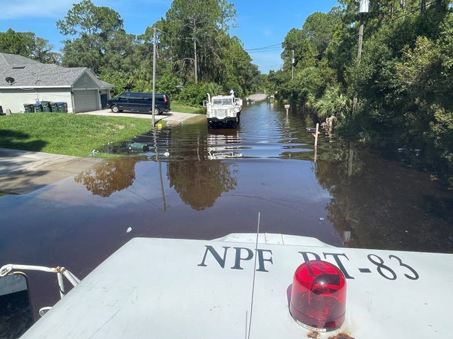 North Port officials monitor flood-impacted streets in the city Saturday morning.