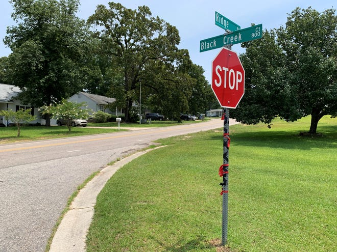 Black and red ribbons tied around the street sign at the corner of Ridge Road and Black Creek Court near where Ashanti Bellamy, 22, was shot and killed May 17.