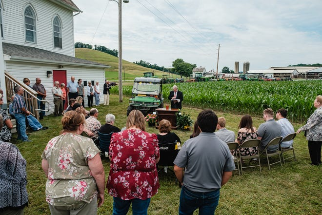 Family and friends gather for a short ceremony behind St. Peter's Lutheran Church in Oldtown Valley, south of New Philadelphia, during the funeral for former Oldtown Valley resident and farmer, Jerry Horn Sr., Saturday, July 10. A cornfield of his farm, seen in the background, is just south of the church.