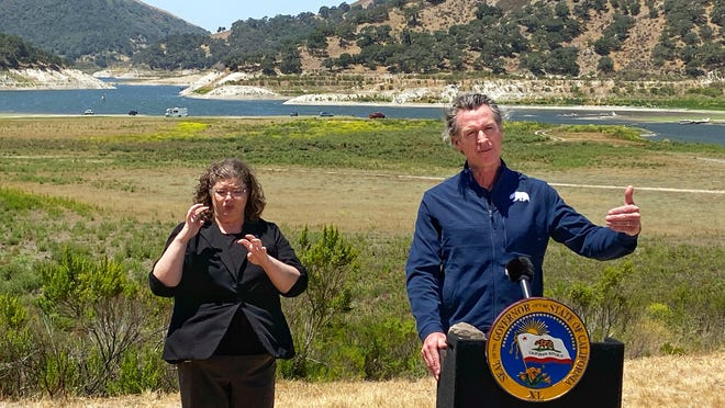 Gov. Gavin Newsom and interpreter Julia Townsend stand at the edge of a diminished Lopez Lake near Arroyo Grande, Calif., Thursday, July 8, 2021. Newsom has asked people and businesses across California to voluntarily cut water usage by 15% amid a drought. Newsom's request demonstrates the growing challenges of a drought that is tied to recent heat waves.