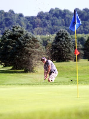 Ramey Ali, of Massillon, hits from a greenside bunker on the Pines Course on Friday at River Greens. Ali was part of group utilizing the facility's stay-and-play package, which head professional Doug Davis said is booked through October. The game has seen a spike in play in the wake of COVID-19.