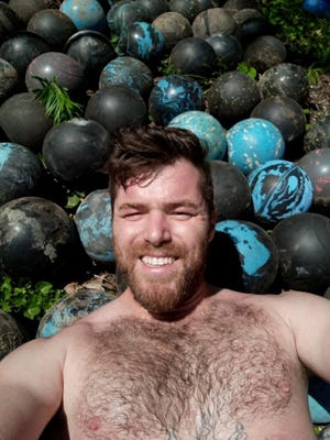 David Olson, 33, poses with some of the bowling balls he unearthed while demolishing the back step of his home.