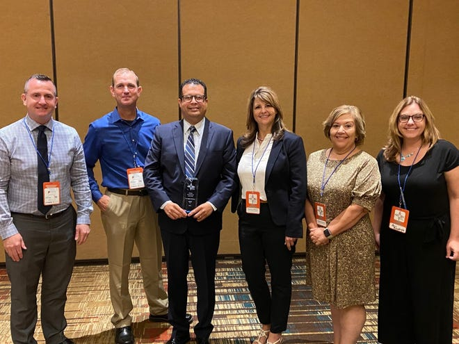 Jeff Spaletta, from left, Jesse Pareo, Miguel Serrano, Sherley O'Brien, Cynthia Donnelly and Amy Himelright pose for a photo after Serrano was named  HR Administrator of the Year